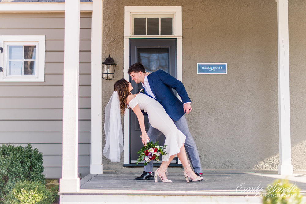 A groom dips his bride and prepares for a kiss on the front porch of the manor house on their wedding day at Fleetwood Farm Winery in Leesburg, Virginia