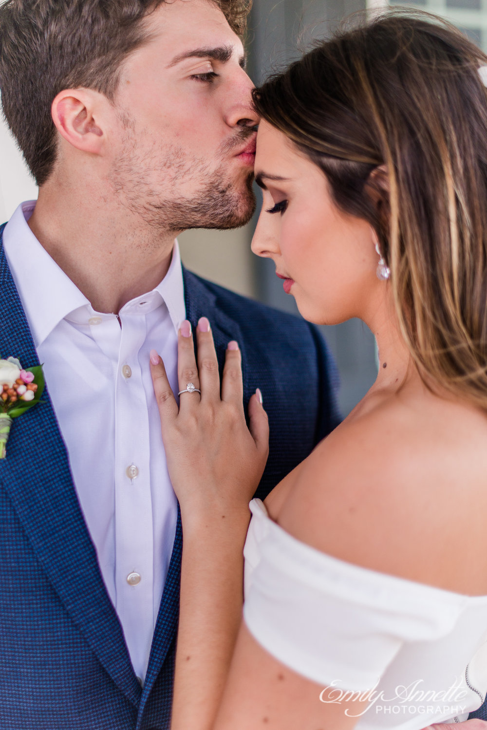 A groom kisses the forehead of his bride as she looks down at her wedding ring on their wedding day at Fleetwood Farm Winery in Leesburg, Virginia