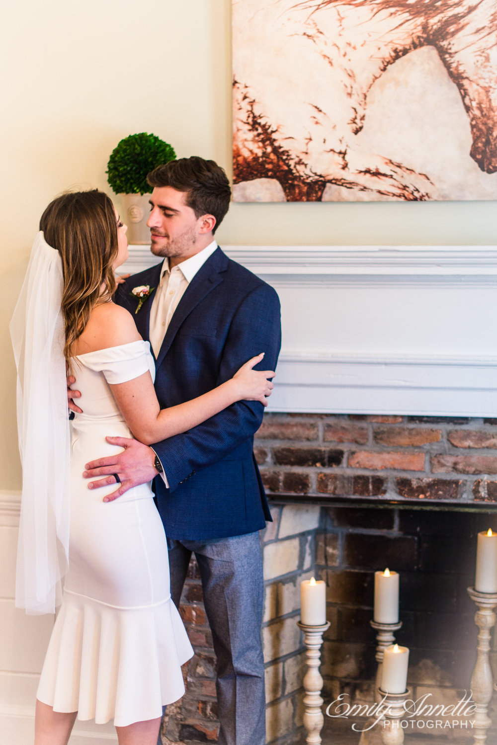 A bride and groom embrace while standing next to a fireplace filled with candles on their wedding day at Fleetwood Farm Winery in Leesburg, Virginia