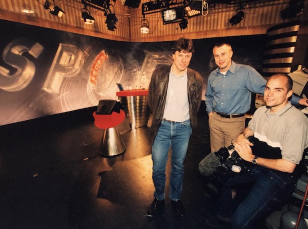 Värmländsk trio i Studio 10.    Den här bilden tror jag togs i samband med ett tidningsreportage för någon av värmlandstidningarna. Det är jag (Karlstad) redaktör Magnus Wilandh (Hagfors) och fotograf Per Frisell (Kristinehamn) som poserar så glatt i gamla Sportnytt-studion. Bilden är den enda jobbild jag hittar på mig själv från 1999.