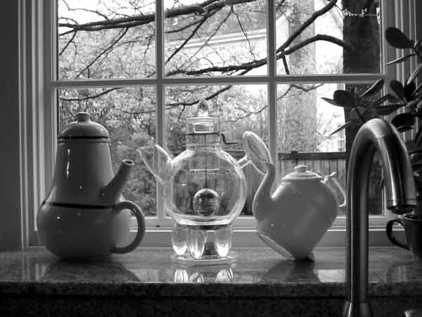 Three teapots: works of art in the window above the kitchen sink. Donald Norman's collection.