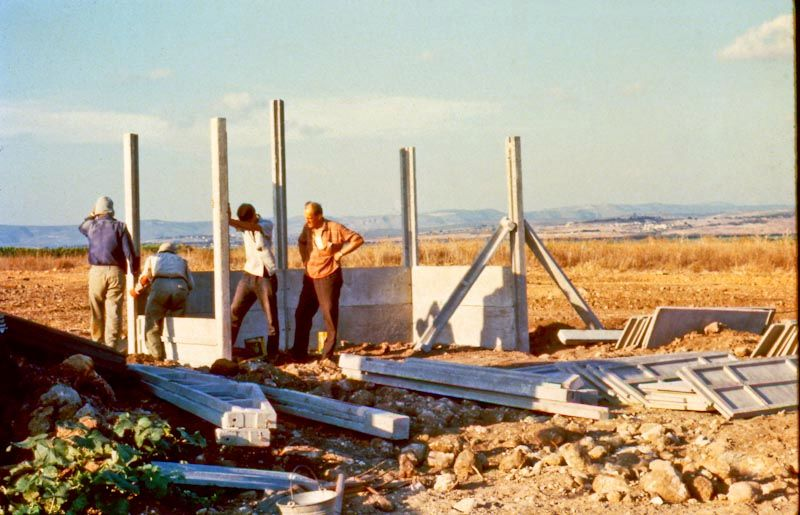 Ein Jahr nach der Gründung des Dorfes bauen Freiwillige die ersten Häuser des Dorfes.