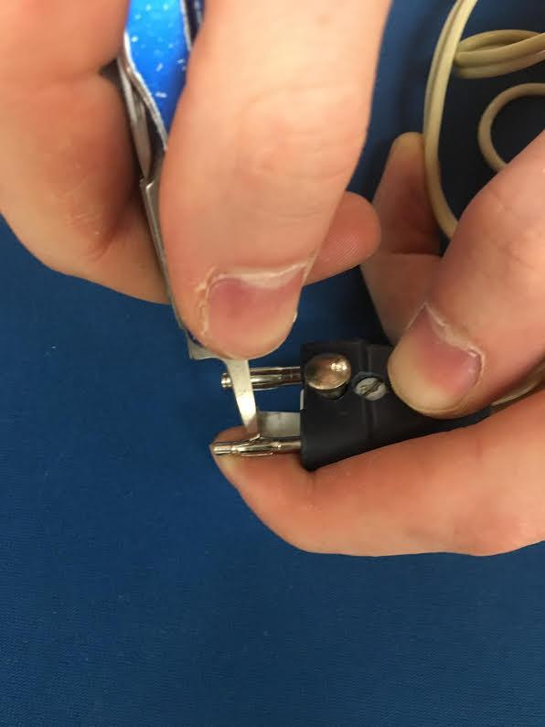 Carefully push a screwdriver into the pin to flare it out