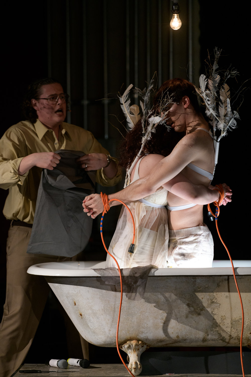 "The angels, restrained in a bathtub, are readied by baritone Shawn Roth, as Mr. X.E., for ""pruning."""