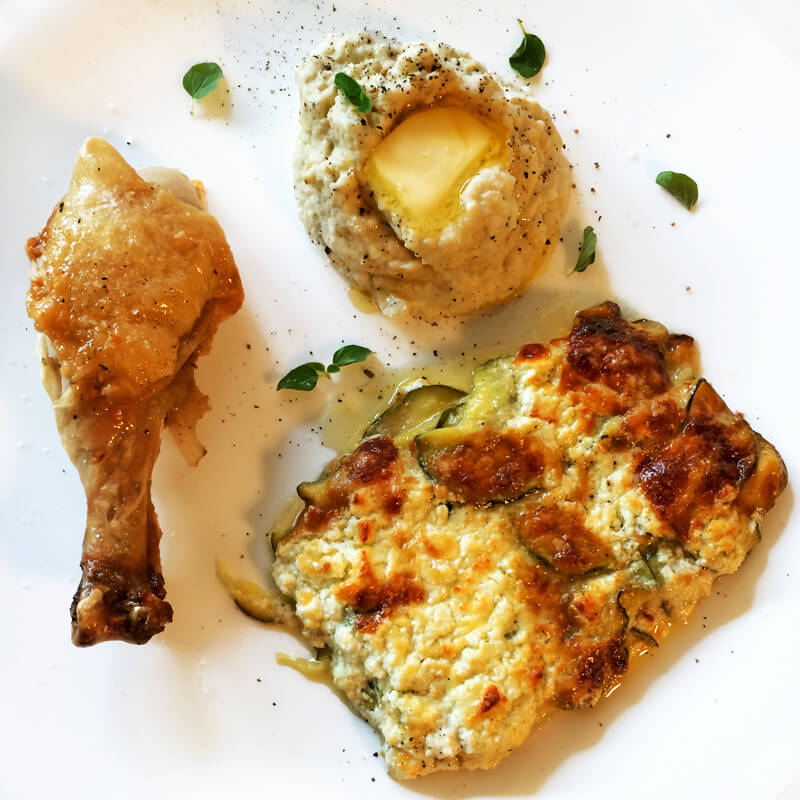 Keto dinner with scalloped zucchini potatoes, mashed cauliflower, and roasted chicken. Enjoy this low carb recipe on the ketogenic diet.