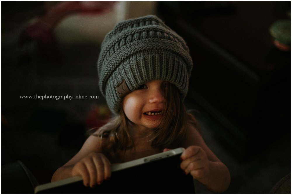 week two - 12/17/17You might see a messy kid in a big hat.  For me, this is my middle child to a T.  The chipped nail polish, chocolate on her face, snack bowl behind her, no clothes, but an iPad in hand and my beanie on.  Her hair a mess because she hates it being fixed and her half smile half cry face.