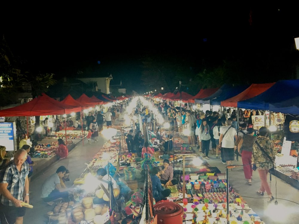 The colorful and vibrant nightly street market scene in Luang Prabang, Laos. The sights, sounds, and smells from this lively night market are enough to entertain anyone. If you want it, they have it here in this 1km long market. Some of our favorite snacks here are the vegetable noodle soup and freshly sliced mango and pineapple.