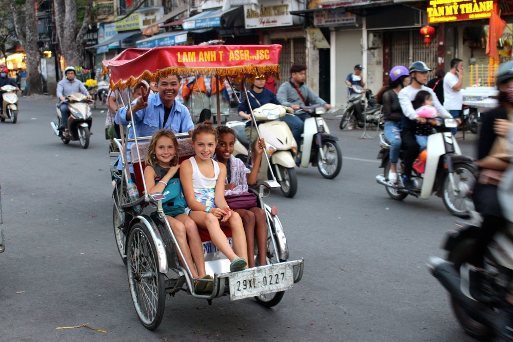 The girls enjoying their bicycle tuk-tuk ride thru the ever busy streets of Hanoi, Vietnam. More than 6 million people live in the Hanoi area, and we are told 5 million of them or more own scooters. Taxes on automobiles here in Vietnam can reach as high as 150% of the purchase price, which alone forces most to buy the more affordable option of a scooter. ($1,300-$1,600).