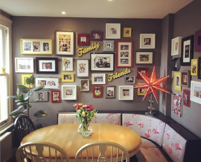 Matthew Shaw 's gorgeous dining corner is edge to edge with collected family photographs in consistent colour frames.