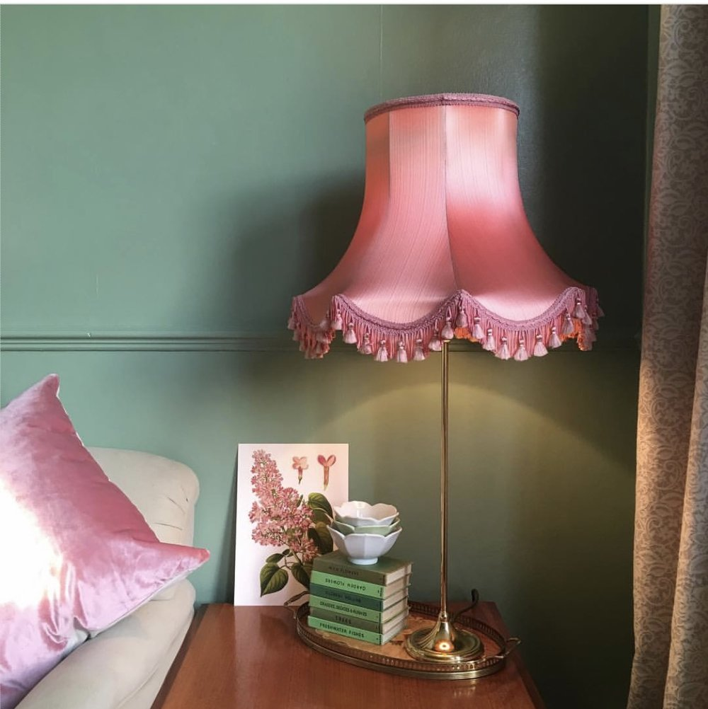 Vintage Amy  adds a retro lampshade and pink cushion. which look stunning against the green of the walls.