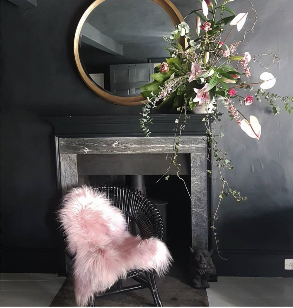 Textural pink sheepskin against black walls looks totally stunning at the home of  Cowboy Kate .