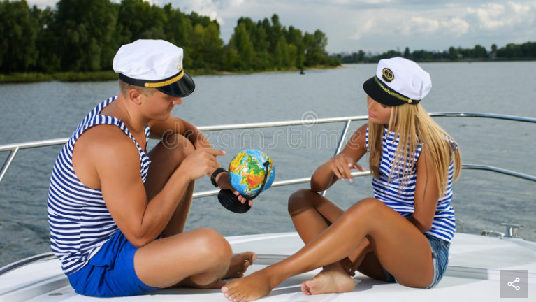 Elegant beautiful couple sitting on a boat with globe looking for the [sic] country to visit (Source: Dreamstime)