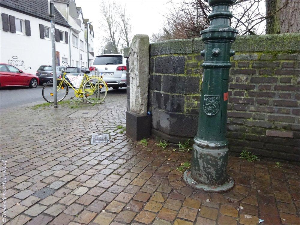 На линии между жёлтым велосипедом и зелёным фонарём (примерно посередине) - за камнем на мосту - было найдено синее яйцо, снесённое пасхальным зайцем.