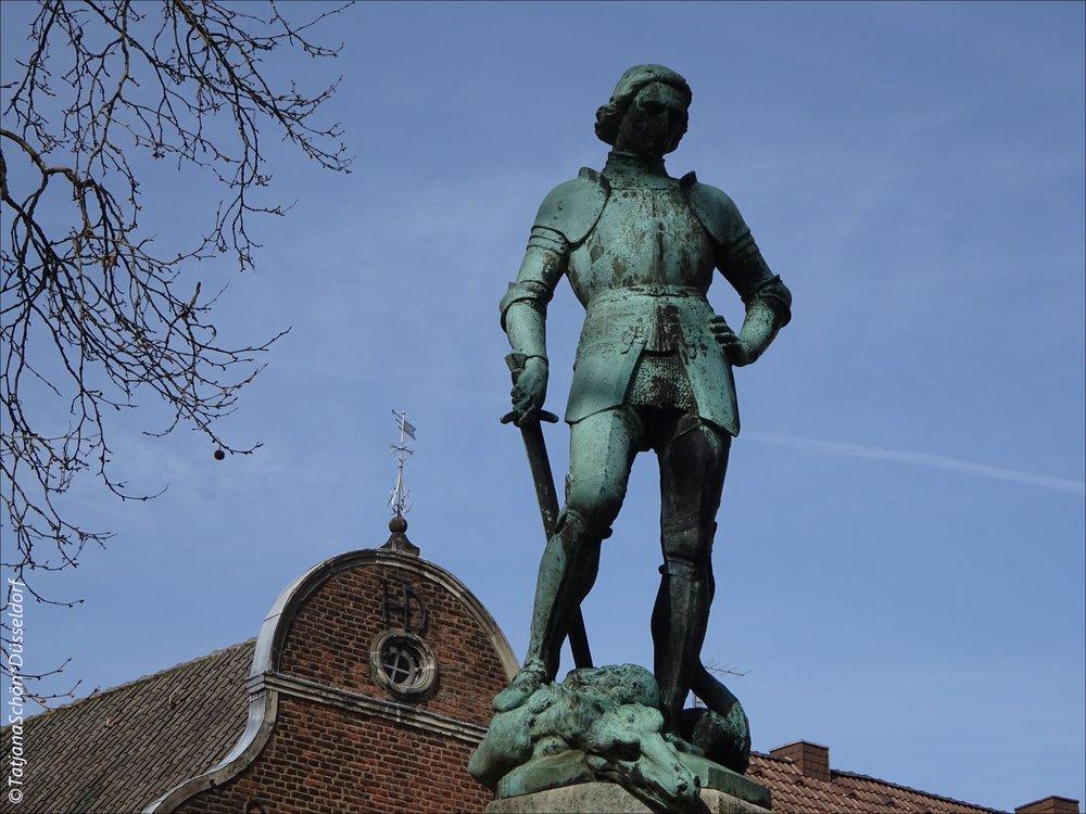 Над главной площадью стоял усталый Святой Георг(ий)...