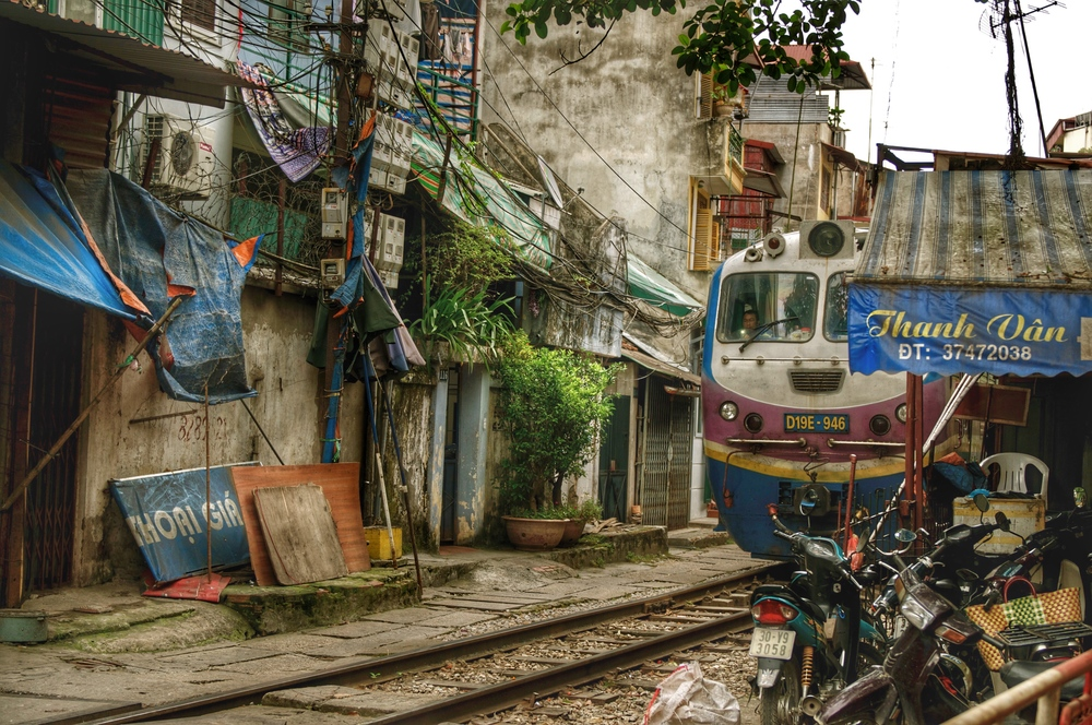 Train routing in the centre of Hanoi, Vietnam, cuts through streets in old town district, on way to Long Bien Bridge.