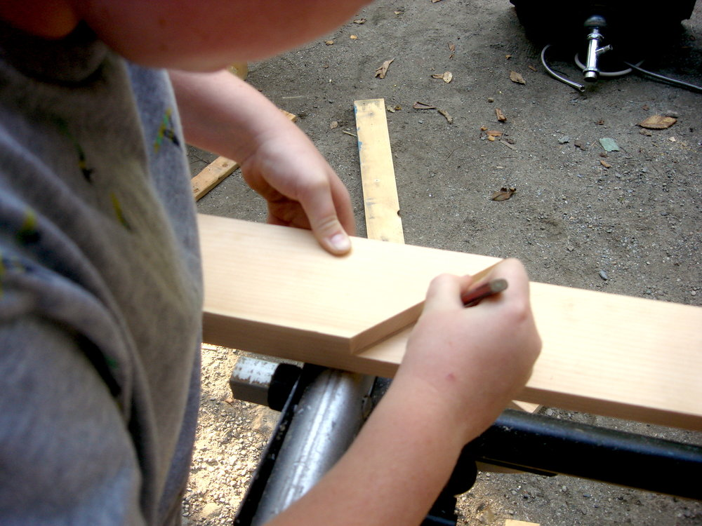 "Noah marks an angle on a 1x4"" board to make a frame for the sudoku board."