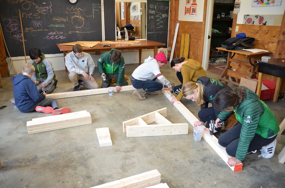 Students practicing with drills by screwing together and taking apart a pair of 2x4's.