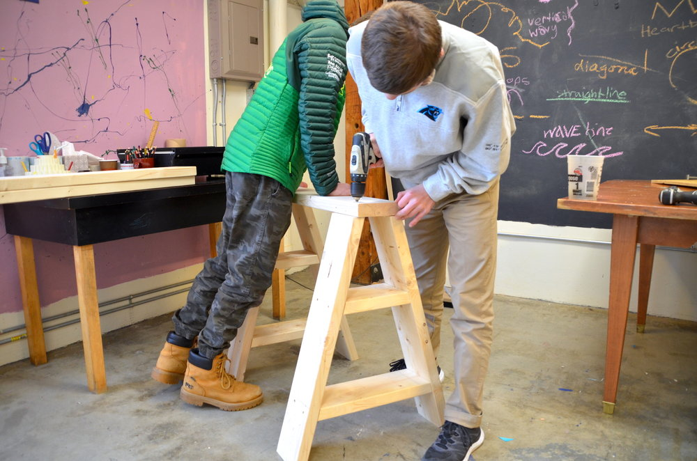 Tommy and Tabor screwing the top board onto their sawhorse.