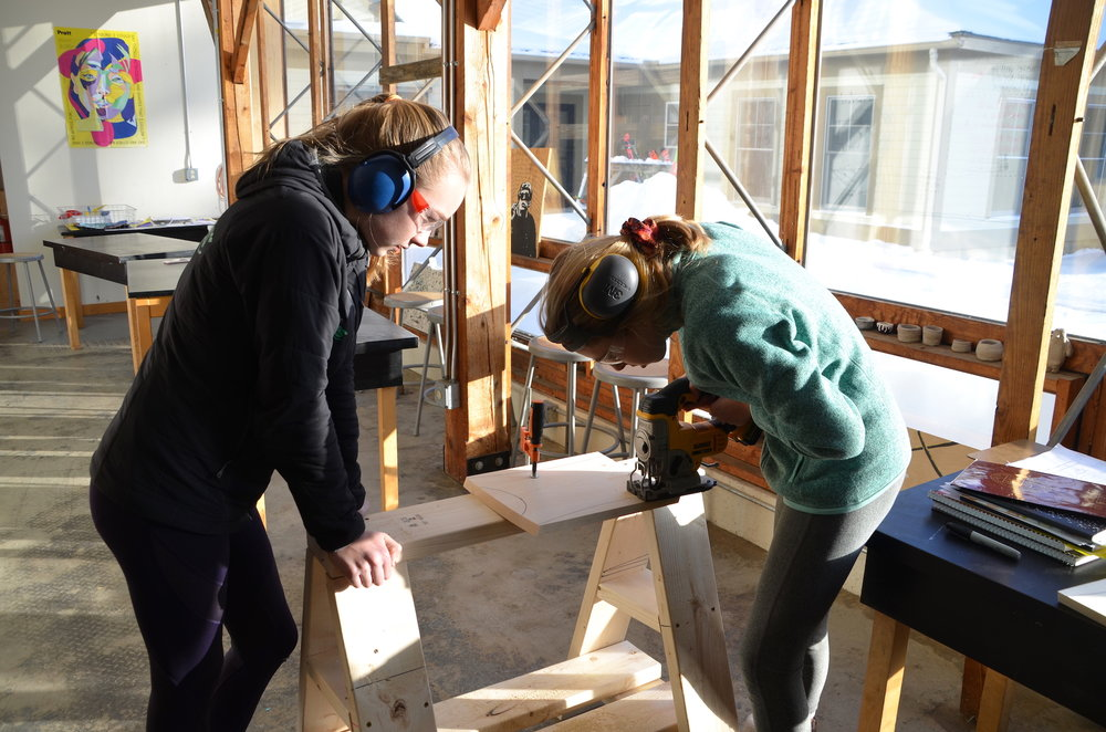 Ella and Whitney using their sawhorse to support a jigsaw cut.