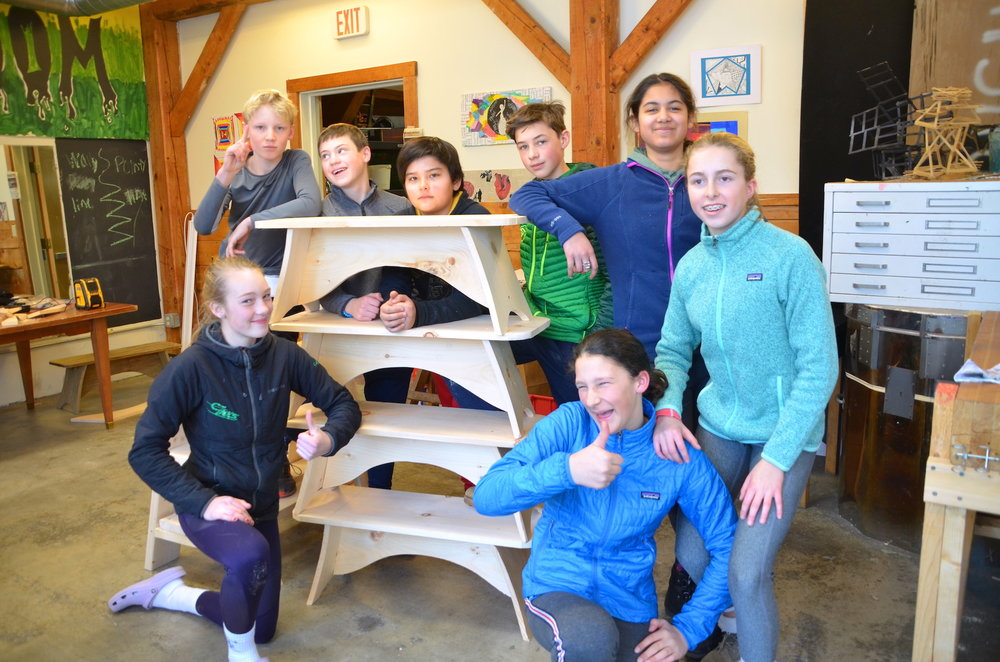 Students standing with their finished benches.