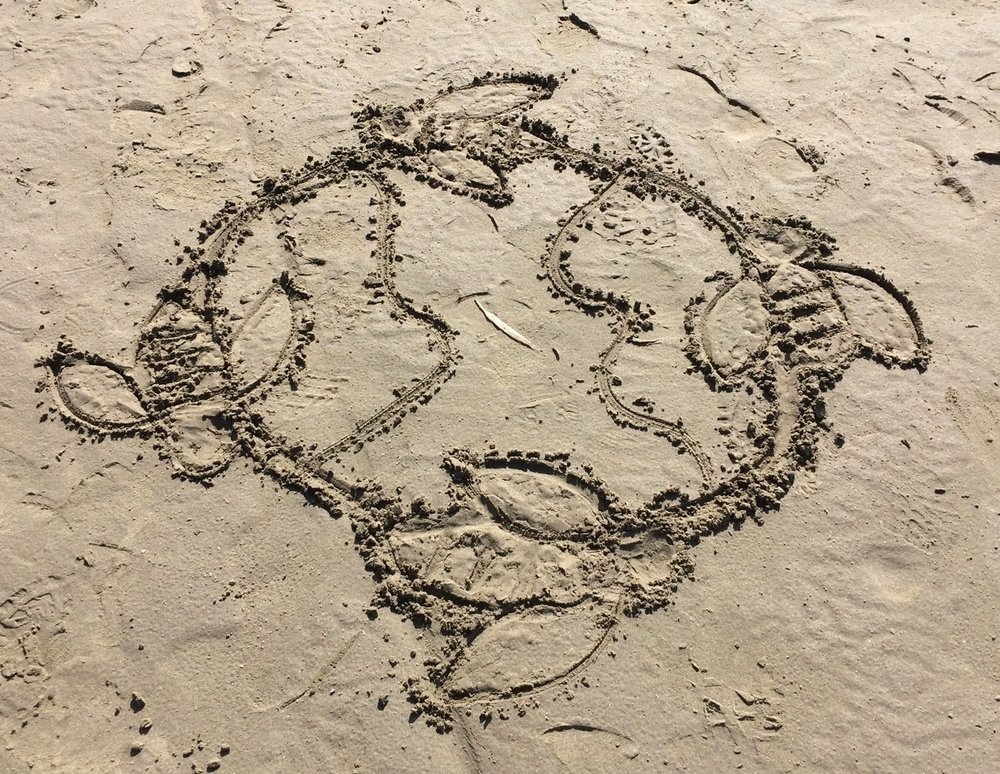 KhalaCloths logo etched in sand