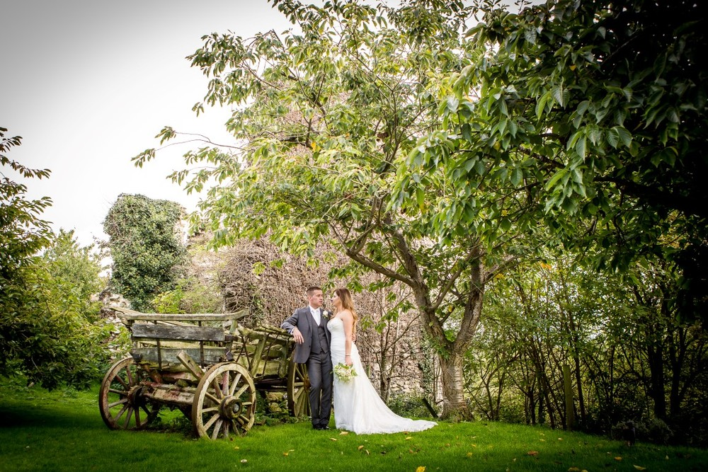 Bride and groom by vintage cart
