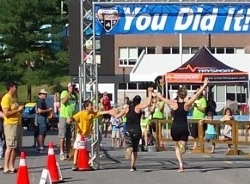 Alison crossing the finish line with a friend and first-timer triathlete.
