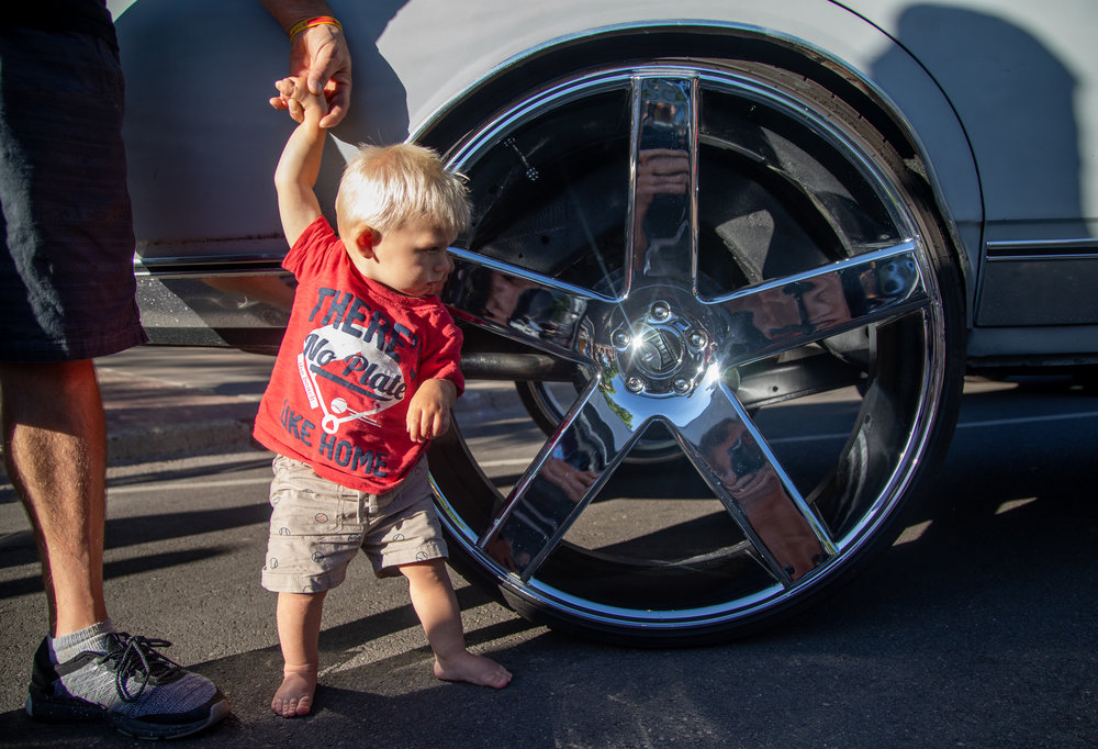 Oliver Friedci, 1, stands next to a 30 inch rim on a 1989 Chevy Caprice Classic at the 2018 Ogden Car Show in downtown Ogden on June 1, 2018.