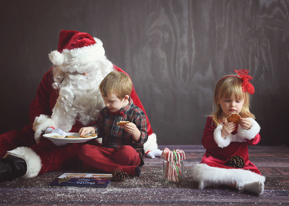 Ana in her own world eat cookie w Santa and Austin WEB.jpg