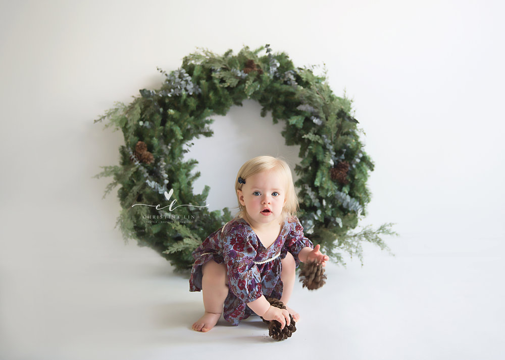 Gracyn hold pinecone in front of wreath CLP.jpg