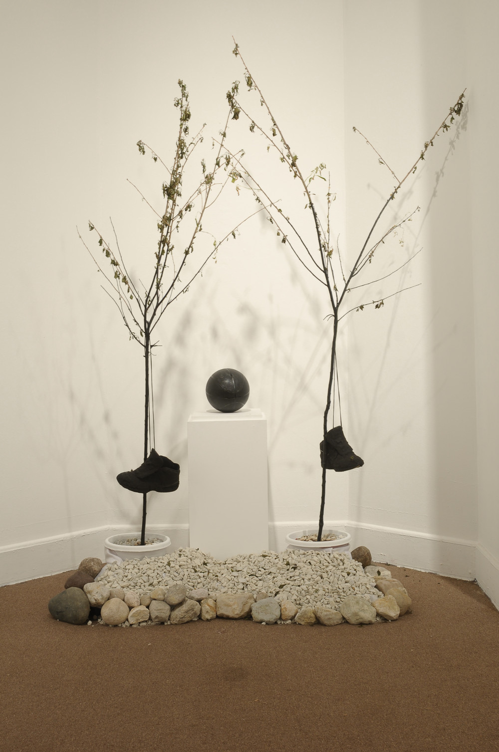 "Throne to the Basketball Gods  stones, sneakers, wooden pedestal, basketball, cherry tree, spray paint  65""x 45""x 86""  2012"