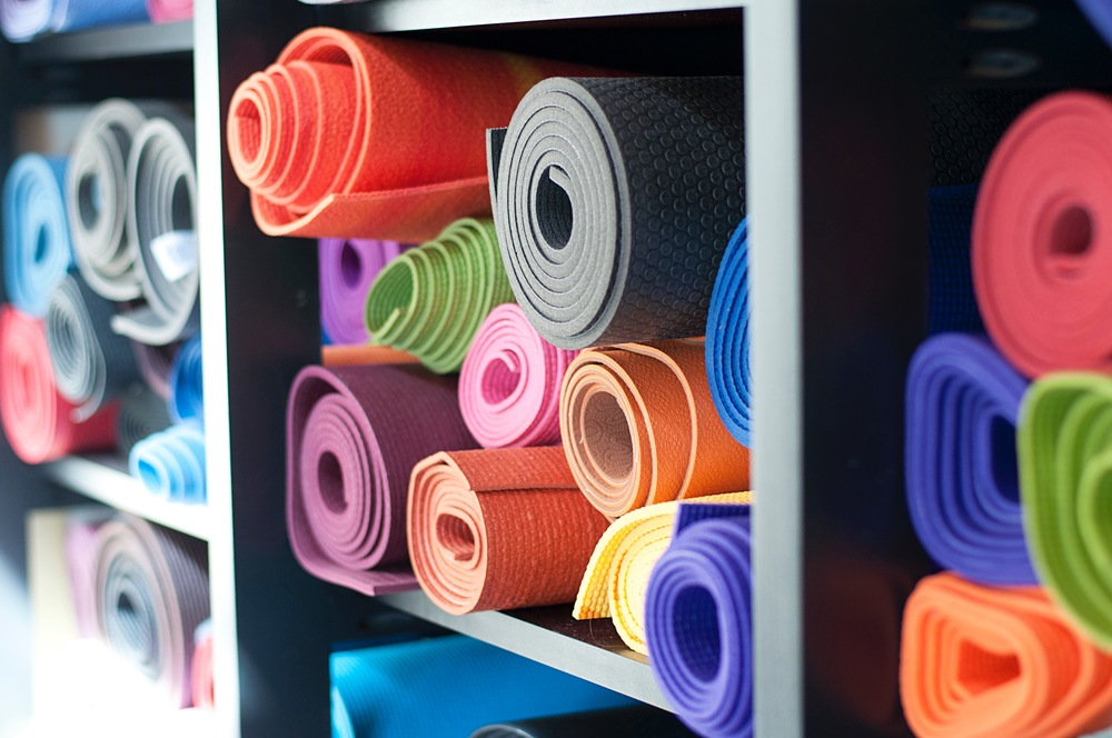 Shelves of yoga mats rolled up.