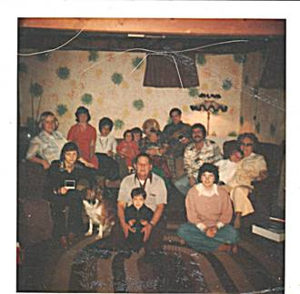 This is a picture of just some of the clan. I am in the left in red, my grandpa in the center on the floor, grandma on right in chair. I am going to guess 1975(ish)