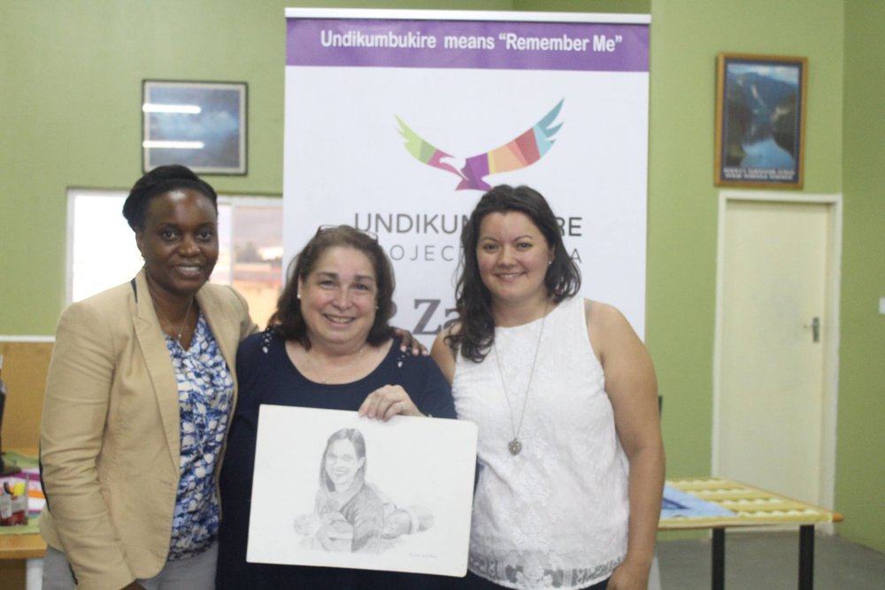 Nancy's mother, Cindy Czaicki, holds a portrait of Nancy commissioned by UP Zambia with representatives from UP Zambia and CIDRZ.
