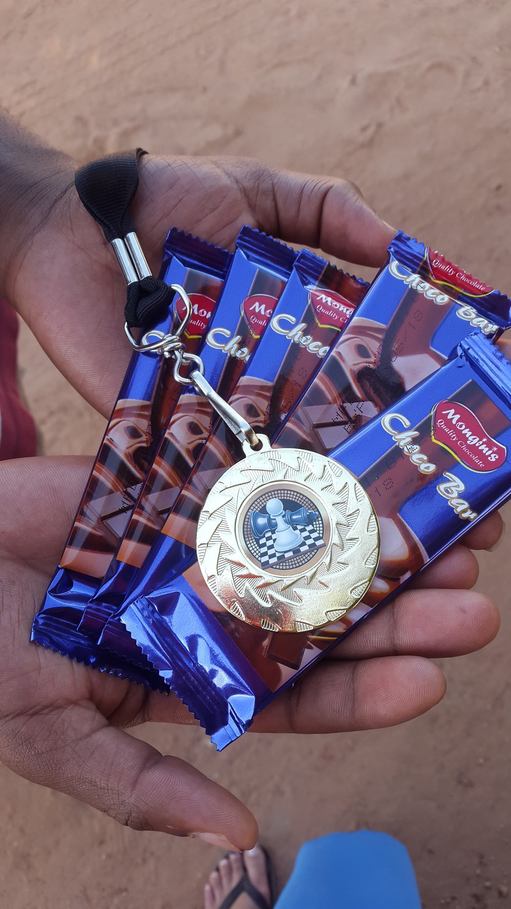 One of the boys proudly showcasing the tournament prizes. Each boy received chocolate for playing but continued to gain more chocolate bars as they progressed through the rounds. The ultimate victor earned the much coveted (and first) UP Zambia Chess Championship Medal.