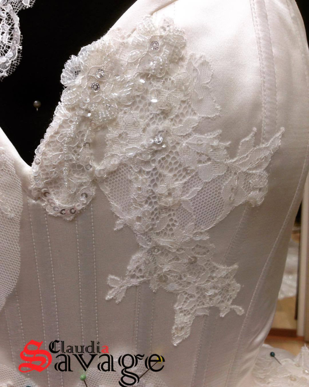 Hand stitched beginnings of lace applique on the corset bodice.