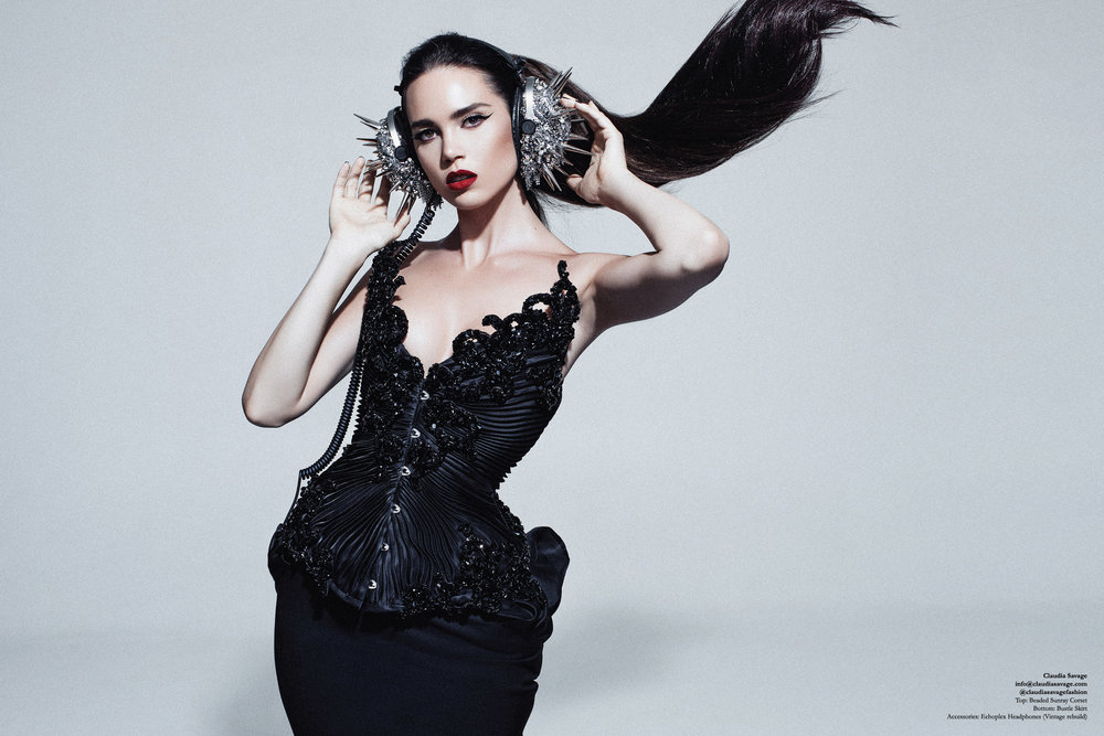 """Model wears a made to measure corset with black silk organza pleating, encrusted with sculptural lace which has been coated in hand stitched jet Swarovski Elements over a black under-bust wool pencil skirt with a sculpted silk organza bustle. The silver """"Echoplex"""" headphones are coated in silver coloured studs and spikes, draped in metallic mesh and hand encrusted with silver Swarovski Elements."""