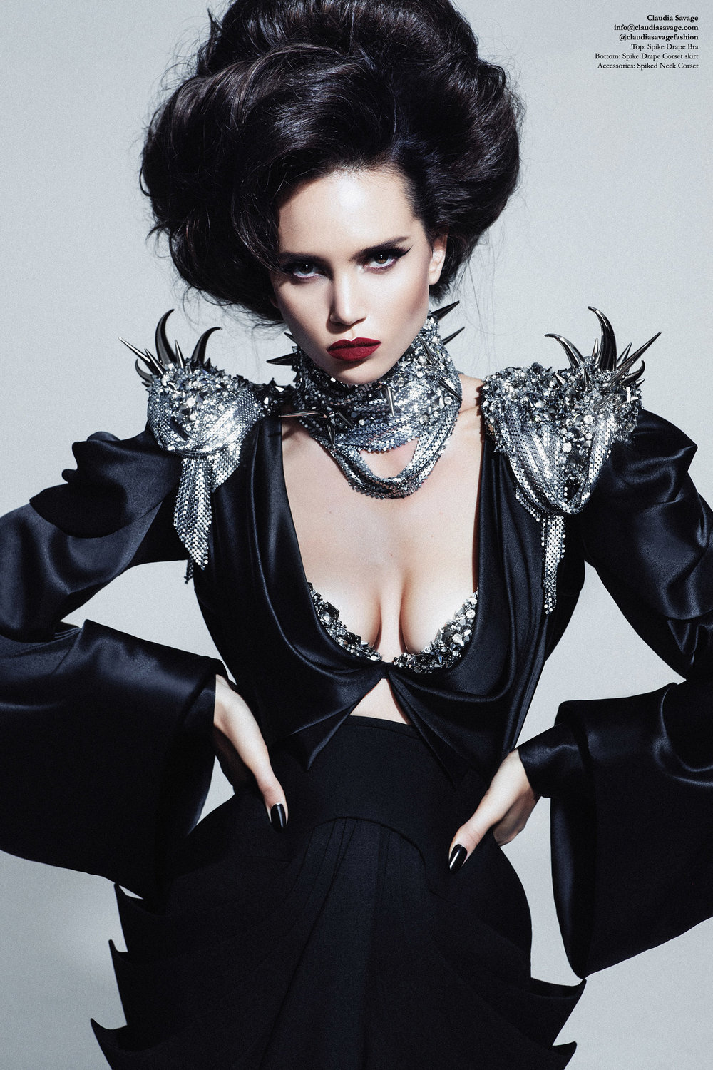 Model wears a black draped silk satin top with Swarovski encrusted exposed bra. The silk top has piked and metallic mesh draped shoulder pads which have been hand stitched with Swarovski Elements. This is worn over a draped wool skirt which features sculptural spiked cowls draped from an under-bust corset. The skirt is fully lined in silk satin and falls into soft folds at the knee. The neck corset features silver spikes and draped metallic mesh which has also be hand stitched with thousands of Swarovski crystals.