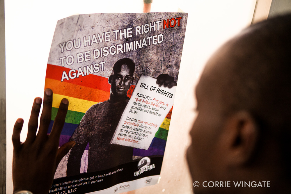 Receptionist Kelly Njoka puts up anti homophobic posters around ISHTAR Wellness center, Nairobi, Kenya
