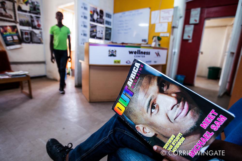 Beneficiary waits to be seen by the nurse in reception reading a magazine, ISHTAR Wellness center, Nairobi, Kenya