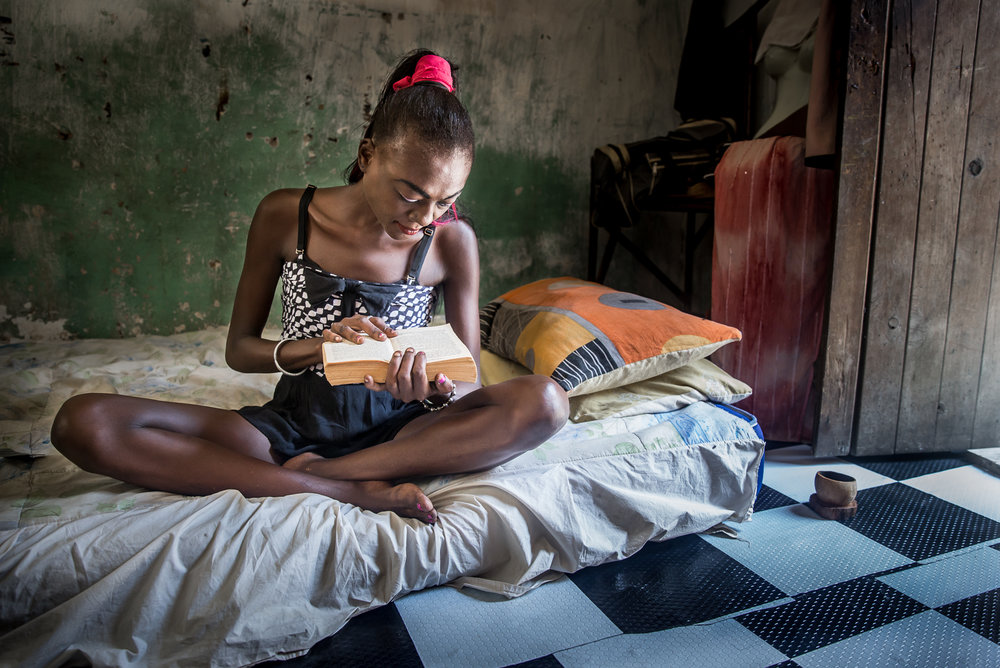 Pheobe Kanana is a sex worker in Watamu, a tourist hotspot on the Kenyan coast. Many young girls visit the coast in hope of finding a white man to take care of them and then fall into drugs and sex work to pay for their habit. Pheobe went to secondary school and still enjoys reading to take her away from reality. Here she reads in her bedsit that she shares with a fellow user and local beach boy. Watamu, Kenya. International HIV/Aids Alliance