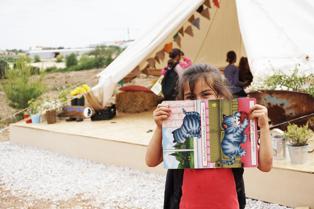 Girl with her new book outside the Children's library in Ritsona