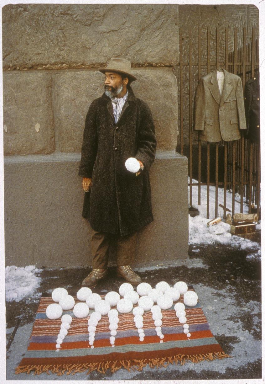 David Hammons - Bliz-aard Ball Sale (1983)  David Hammons verkoopt sneeuwballen op Cooper Square in Manhattan, New York. In dit stukje performance art rangschikt de kunstenaar een hoop sneeuwballen van groot naar klein. Hoe groter de sneeuwbal, hoe duurder. Met deze kunstactie klaagt Hammons niet enkel de vercommercialisering van kunst aan, hij reageert ook op de urbane verschoningsoperatie van de stad New York. Sneeuwballen op een tapijtje. Prachtig.  Prachtig in het genre: 'Openbare verkoop van zeer vergankelijke producten'