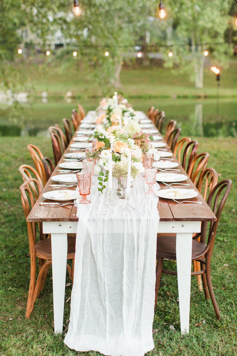 wood table setting outdoors with twinkley lights