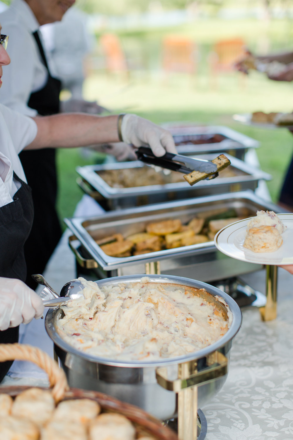 caterers serving mashed potatoes and vegetables