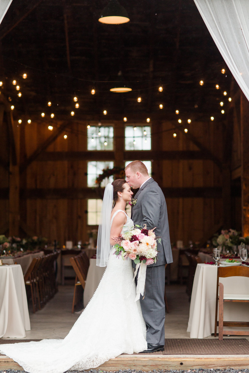 bride and groom kissing outside barn under twinkly lights