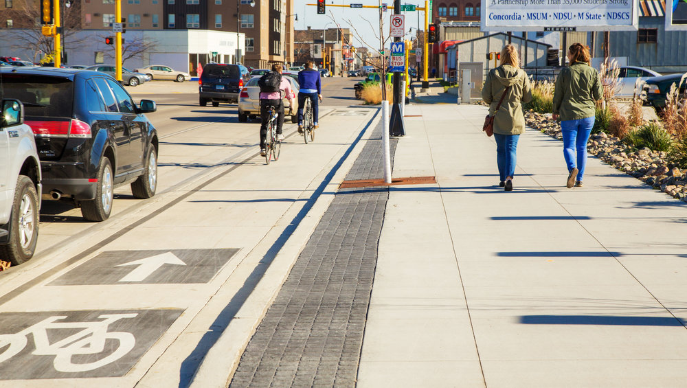 The design creatively accommodates safe travel for bicyclists along an elevated and protected lane, pedestrians via curb extensions and drivers with improved striping and turning movements downtown.