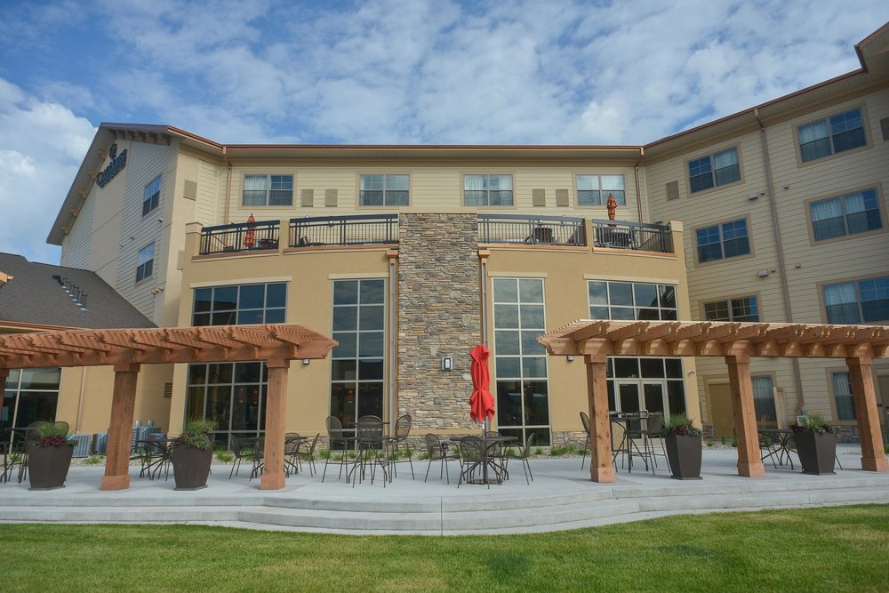 Clubhouse Hotel & Suites shares a back yard space with Porter Creek. Land Elements designed this patio design at the hotel, including pergolas and seating for guests.
