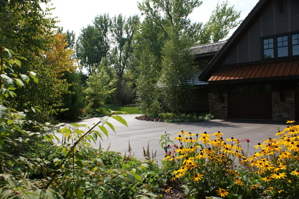 Driveway is surrounded by planting beds and flower gardens
