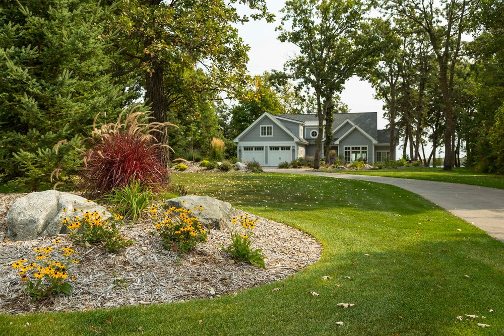 Berming, natural stone outdroppings, and a variety of colorful perennial plantings create a unique entry sequence for this beautiful home on Pelican Lake.